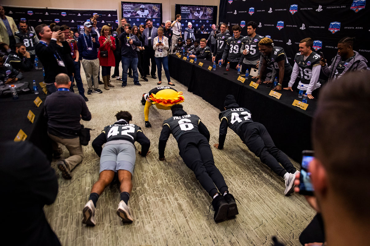 Three football players and a yellow sun mascot do pushups in front of a room of spectators