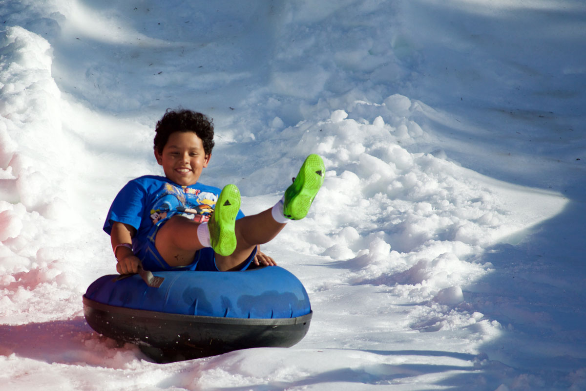 A young boy wearing a blue shirt and green shoes rides a snow tube