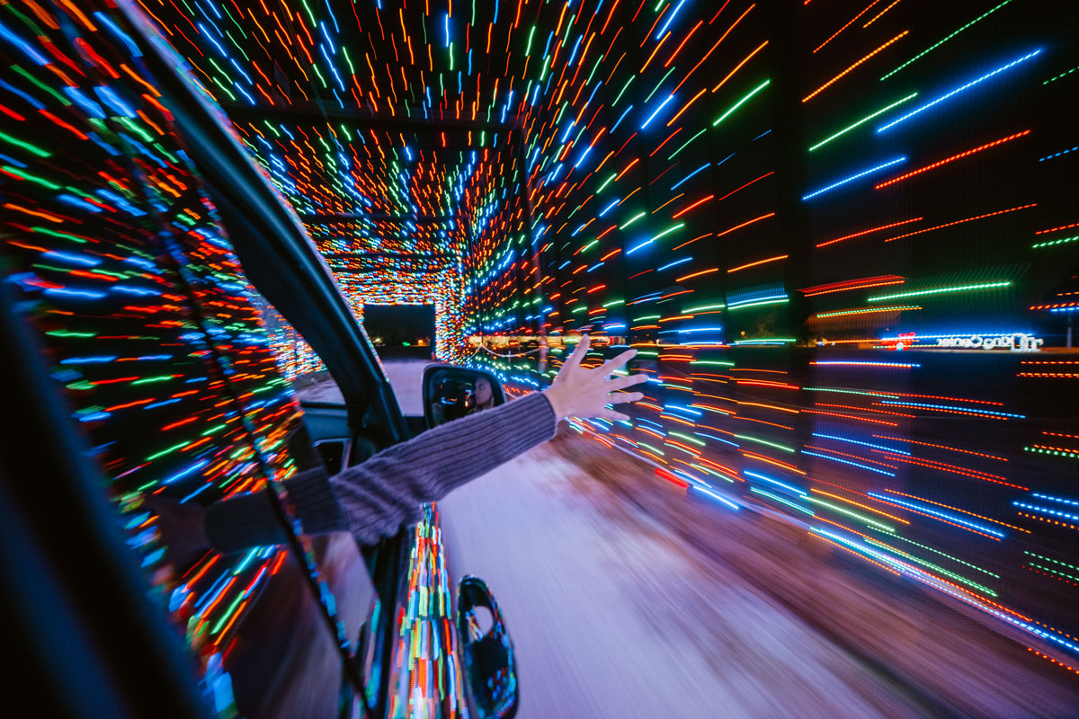 A hand and arm sticks out of a passenger window in a car with blurred colorful lights that make a tunnel