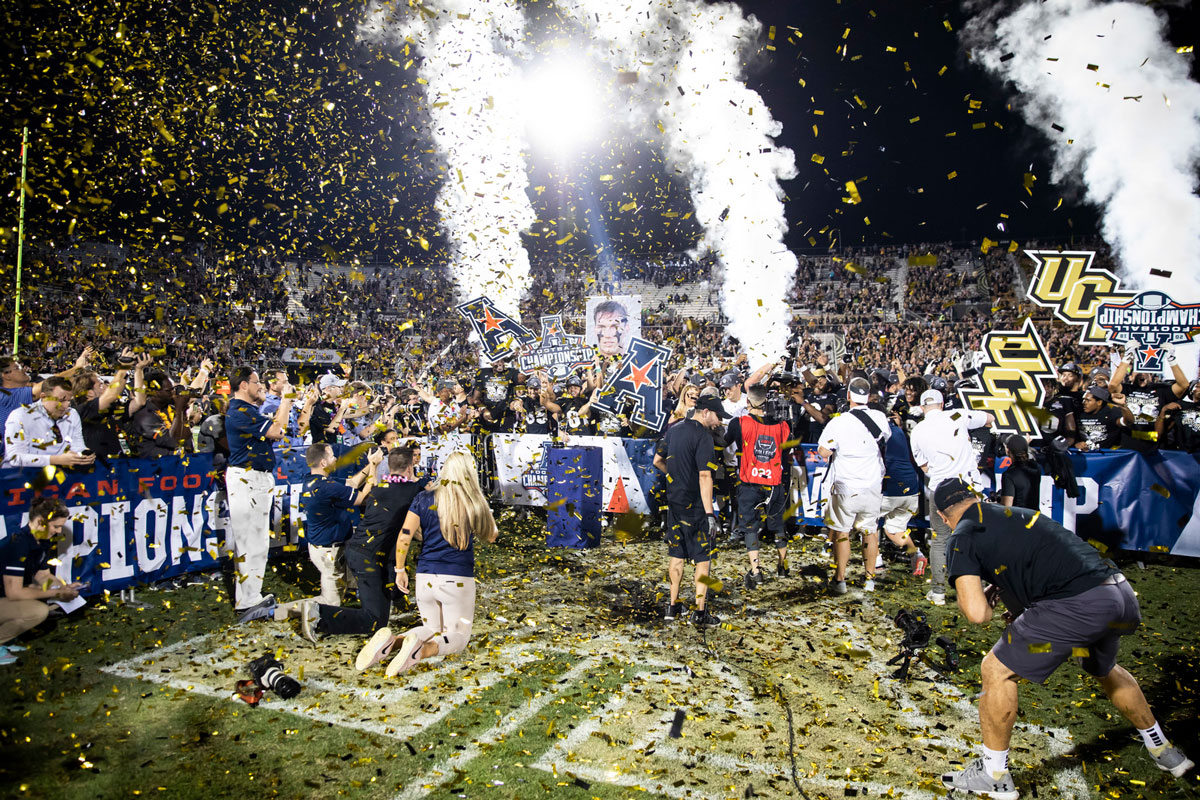 Confetti and smoke fill the air as team celebrates on football field