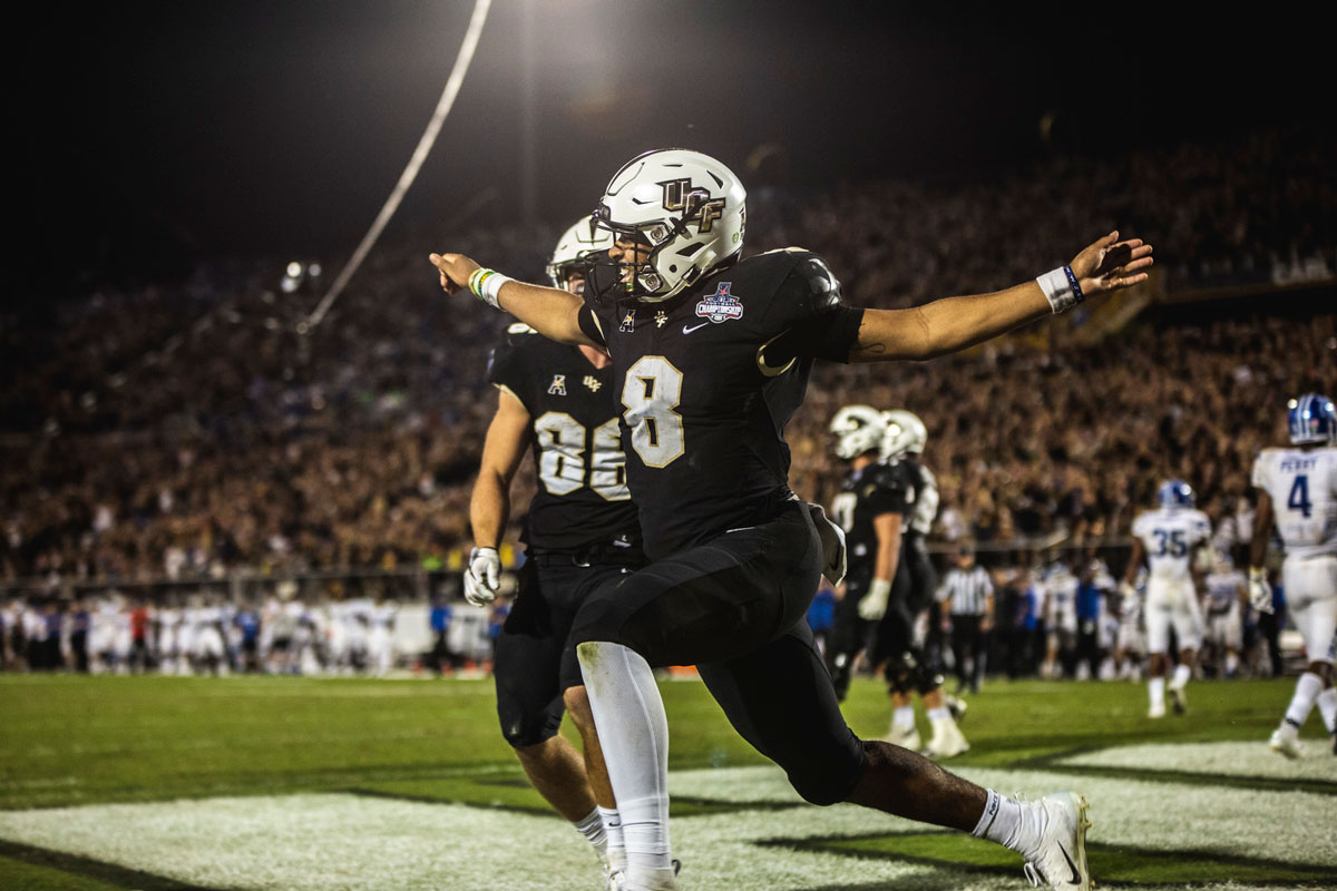 A football player wearing a black uniform and white helmet runs in the end zone with his arms extended like wings