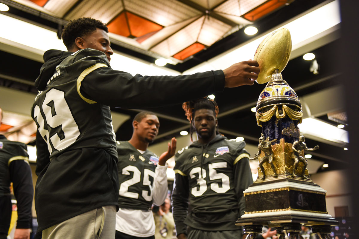 Three football players admire the Fiesta Bowl trophy