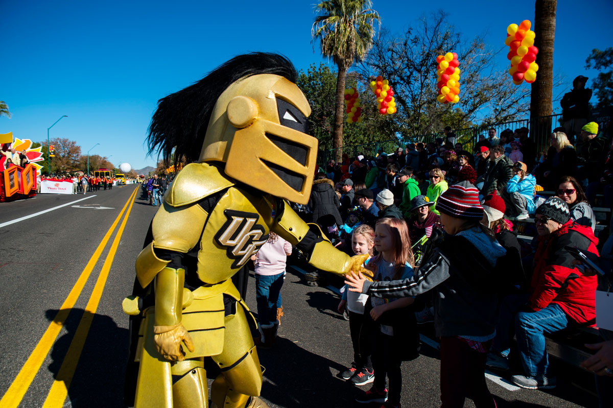 UCF mascot Knightro shakes hands with children.