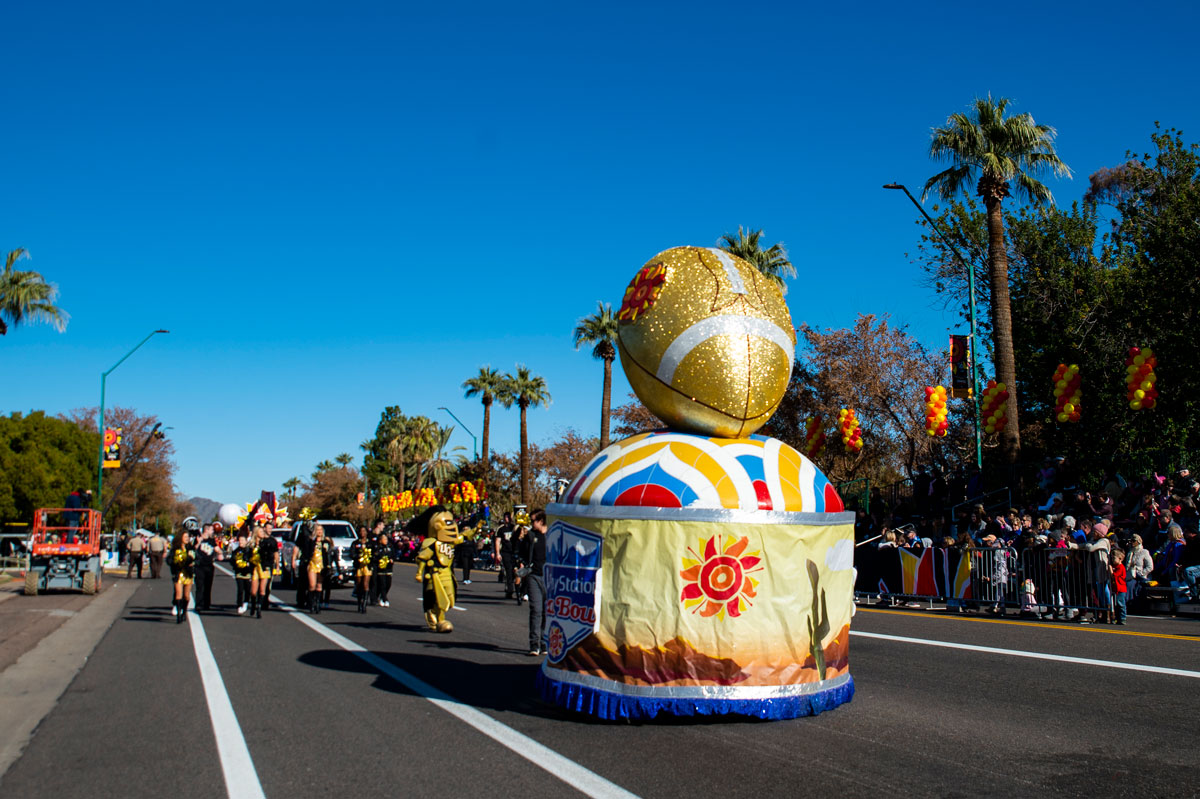 Parade float of a glitter football trophy as it makes it way down the street on a cloudless blue sky day.