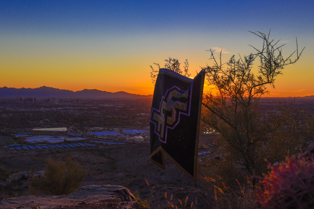 Blue and orange sunset with a UCF flag hanging on a tree