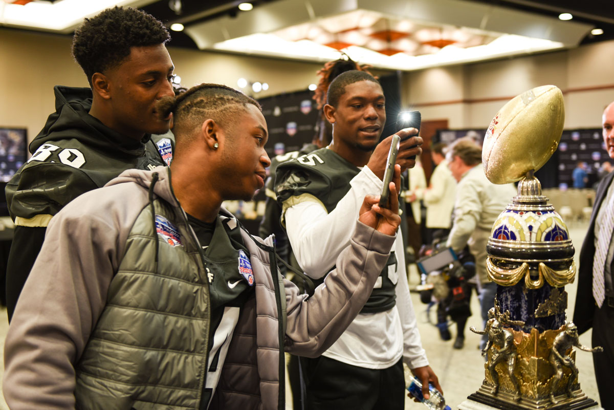 Three football players take photos with their cell phones of gold football-shaped Fiesta Bowl trophy