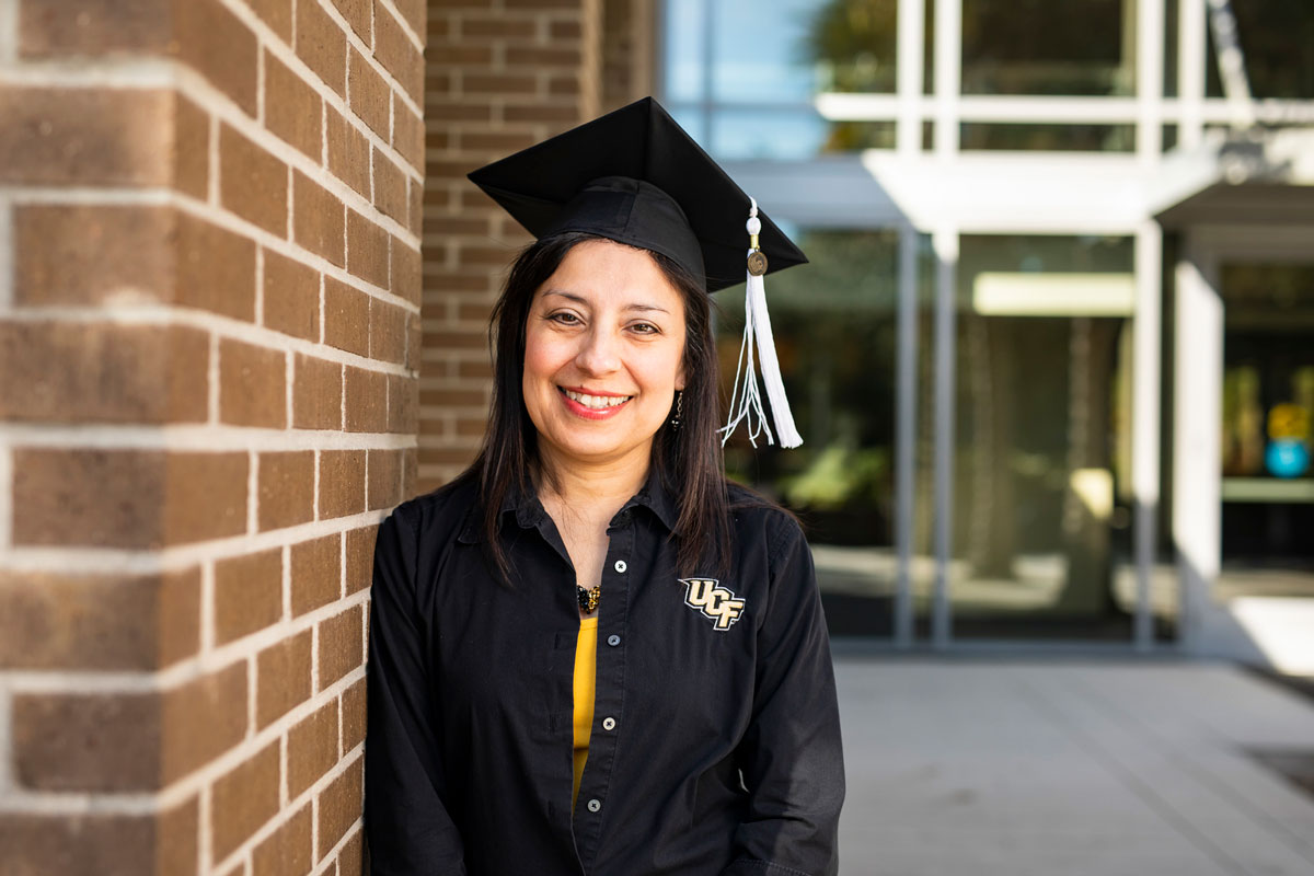Woman with dark hair and black long sleeve shirt with UCF logo poses in black graduation cap and black and white tassel next to a brick wall