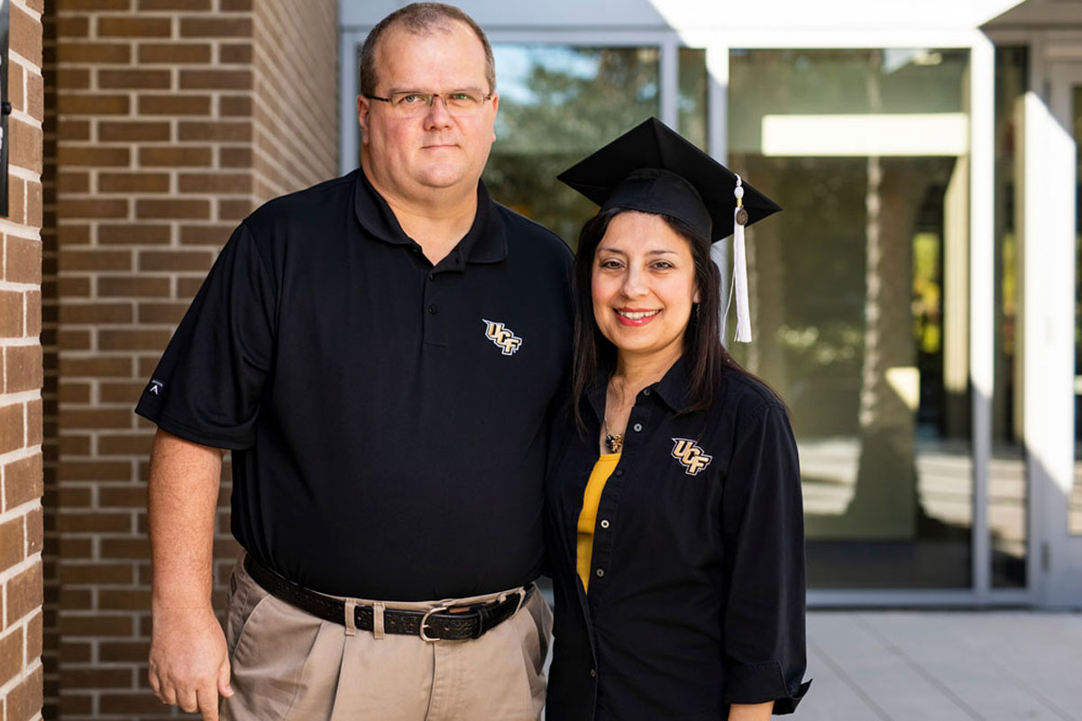 A tall man wearing a black t shirt, glasses and khaki pants puts his arm around a woman wearing a black graduation cap and black long sleeve shirt in front of a brick and glass building