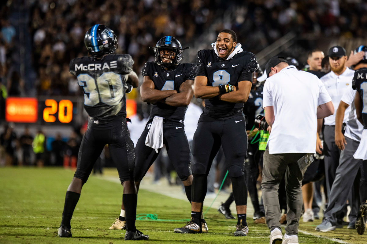 Three UCF players wearing black uniforms pose with arms crossed facing each other