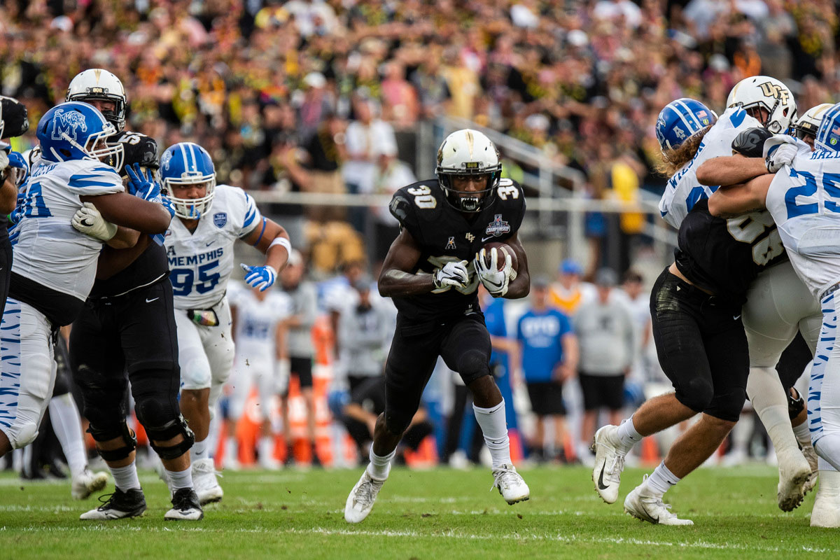 Running back Greg McCrae wearing a white helmet and black uniform runs through a hole one the field as his teammates block Memphis defenders on either side of him.