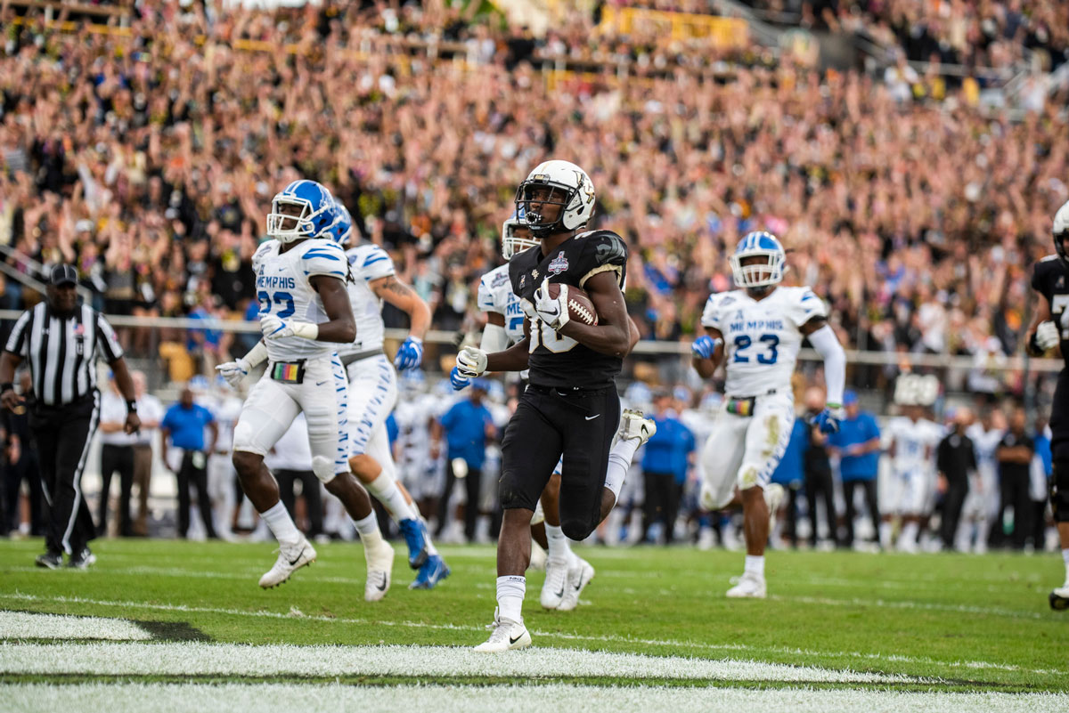 UCF player Greg McCrae wearing a white helmet and black uniform runs into end zone with Memphis defenders trailing him