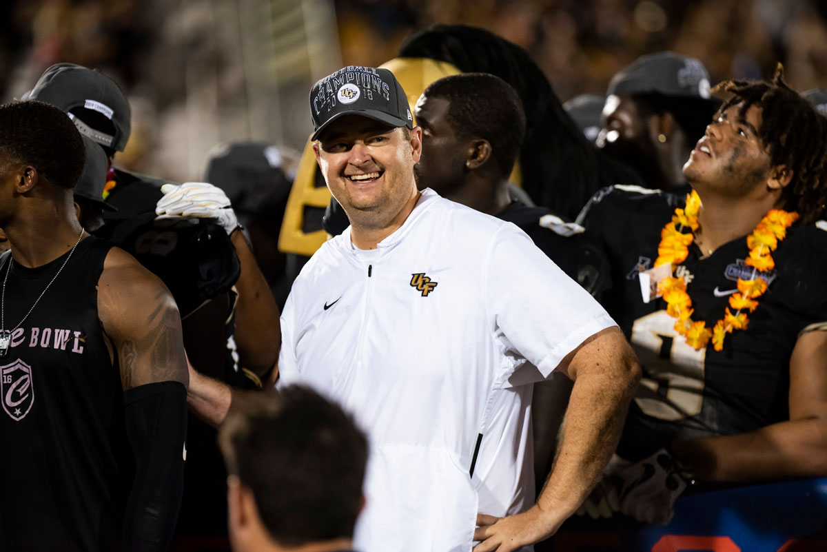 football coach Josh Heupel wearing a white polo shirt and gray hat poses with hand on hip and smiles