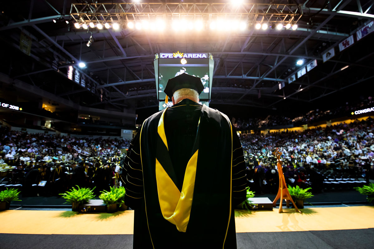 A man wearing graduation regalia stands on a stage and looks out at a crowded arena