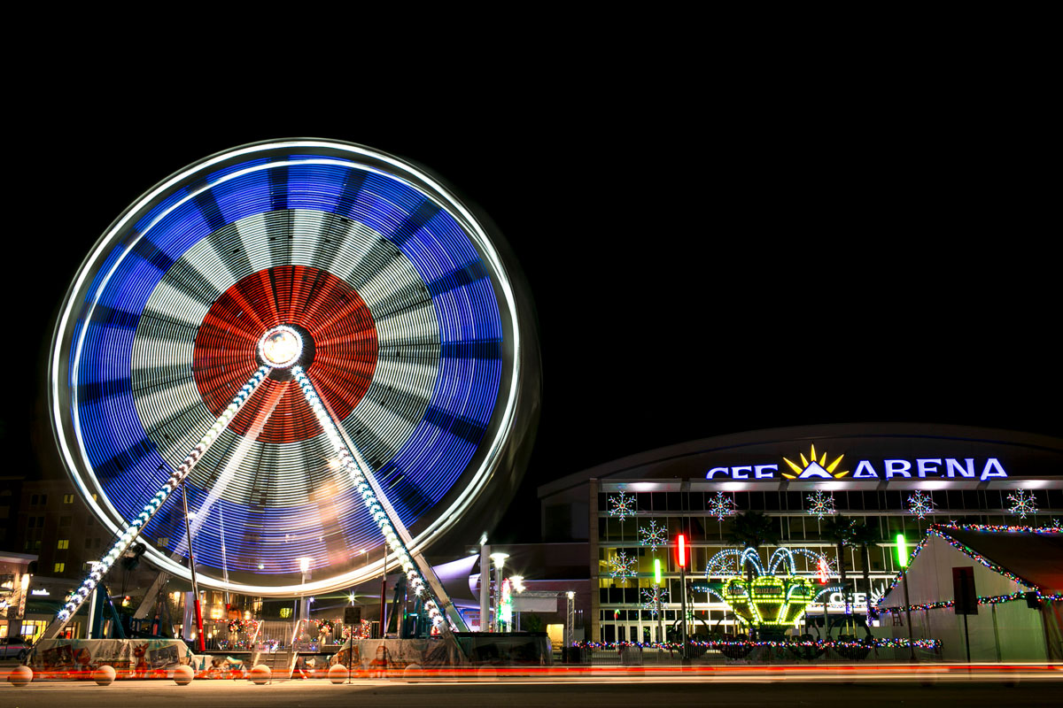 Ferris wheel spins at night with red white and blue colors and CFE Arena in the back ground