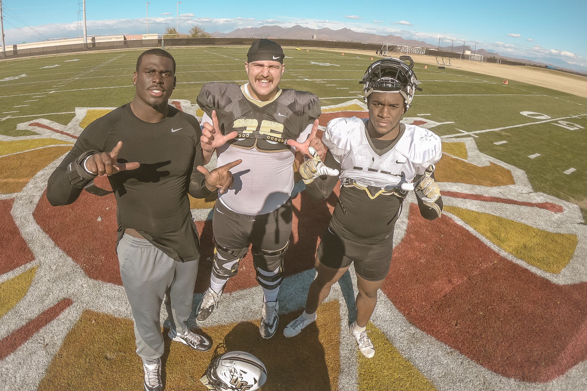 Three UCF football players stand on football field making L shapes with their hands on a sunny day
