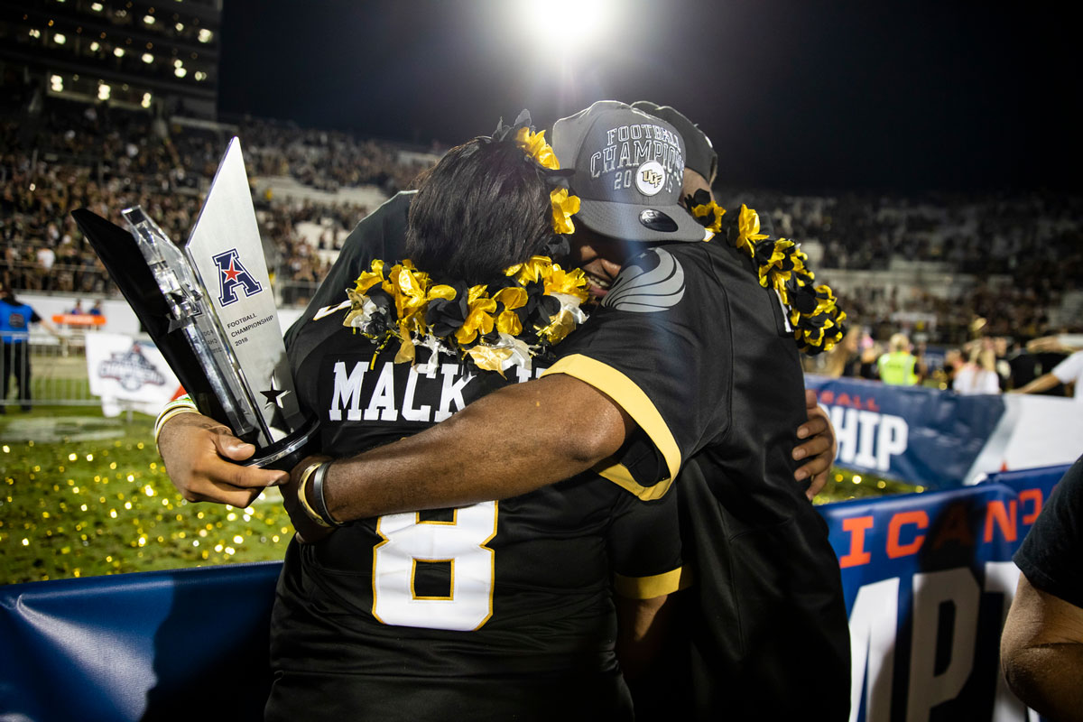 Darriel Mack hugs his parents while also holding a gray trophy