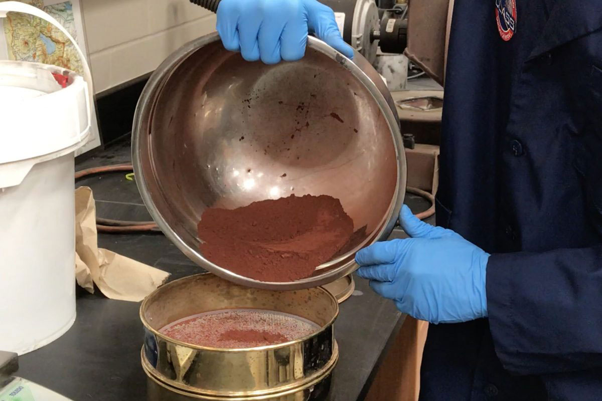 Hands wearing blue gloves hold a metal bowl filled with red-brown dirt