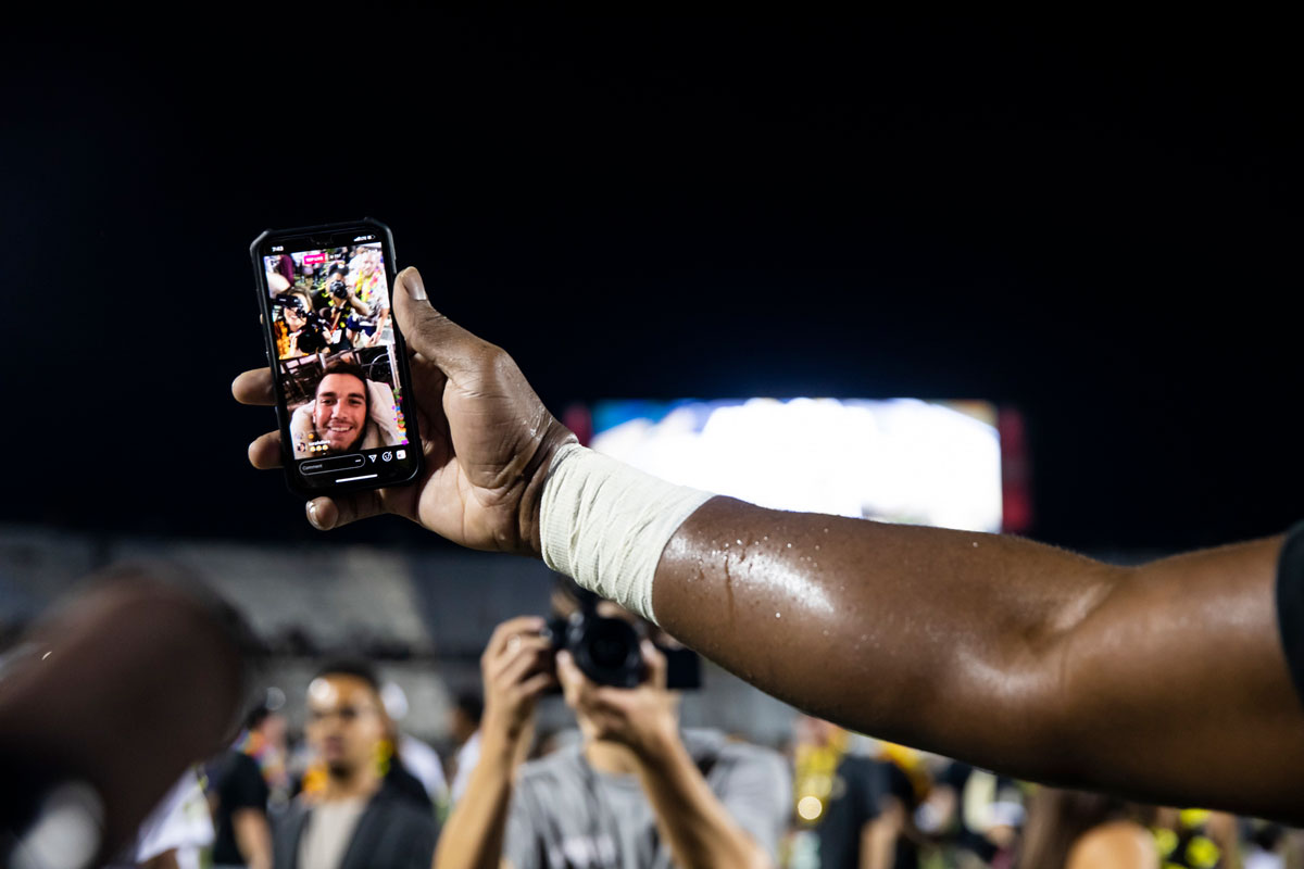 Closeup of an arm holding a phone with McKenzie Milton on screen