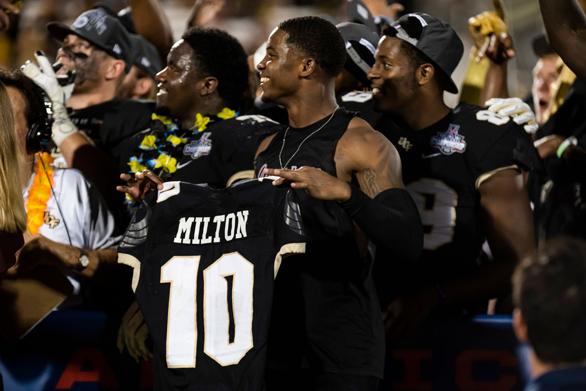 Football players hold #10 Milton black jersey