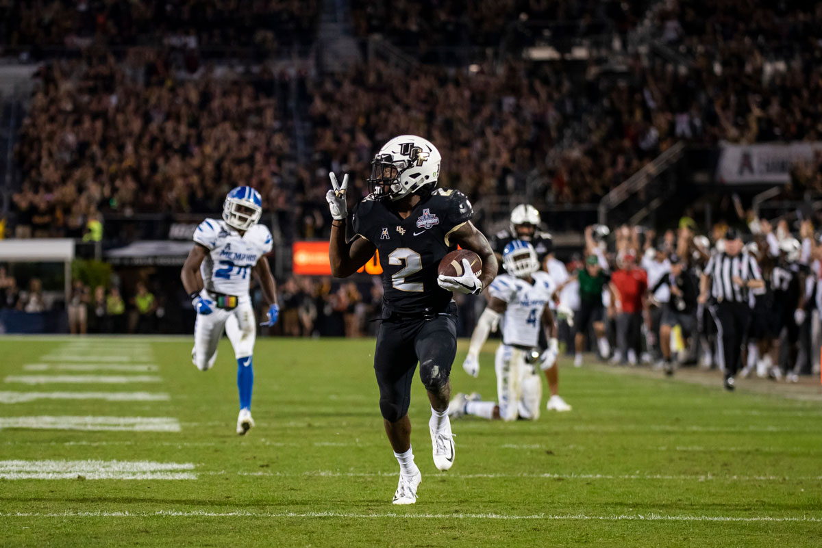 UCF running back Greg McCrae streaks down field holding #2 sign with his fingers as Memphis players chase him down field