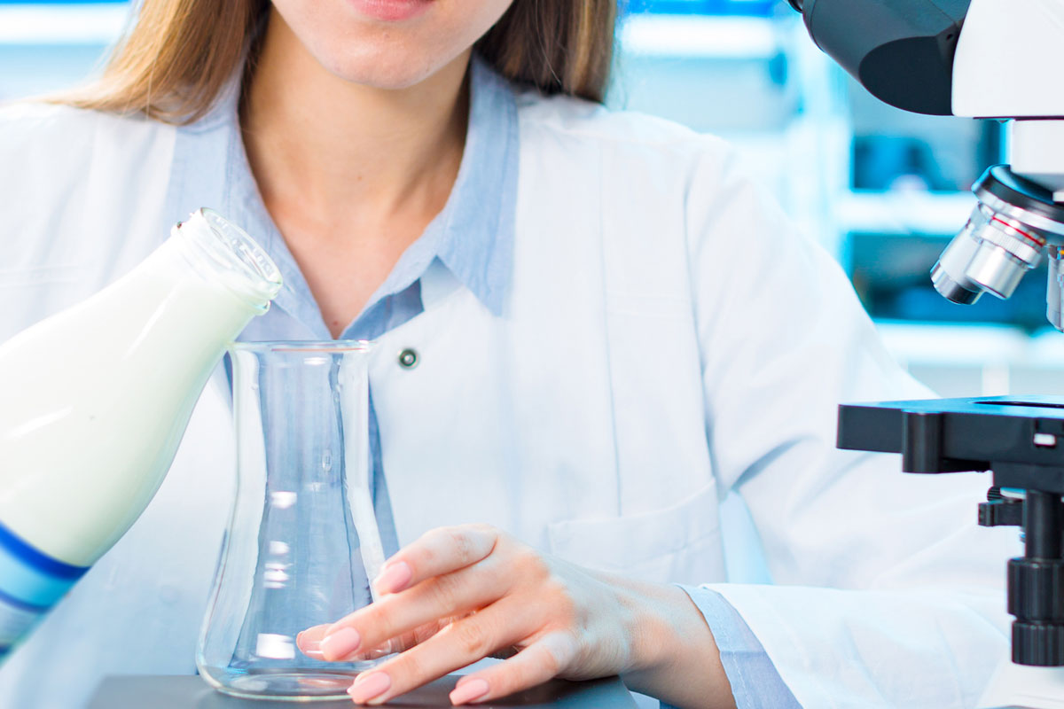 A woman wearing a white lab coat pours milk into a glass beaker in a lab with a microscope nearby