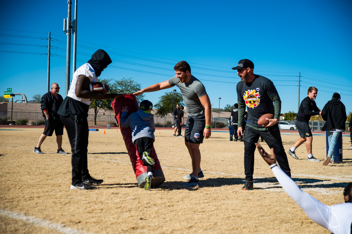 A child tackles a tackling dummy with football players supervising on a dirt lot