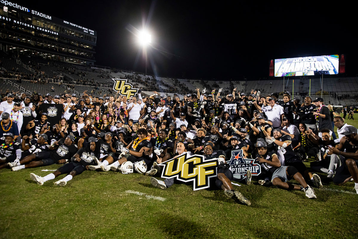 Football team poses with UCF signs on field