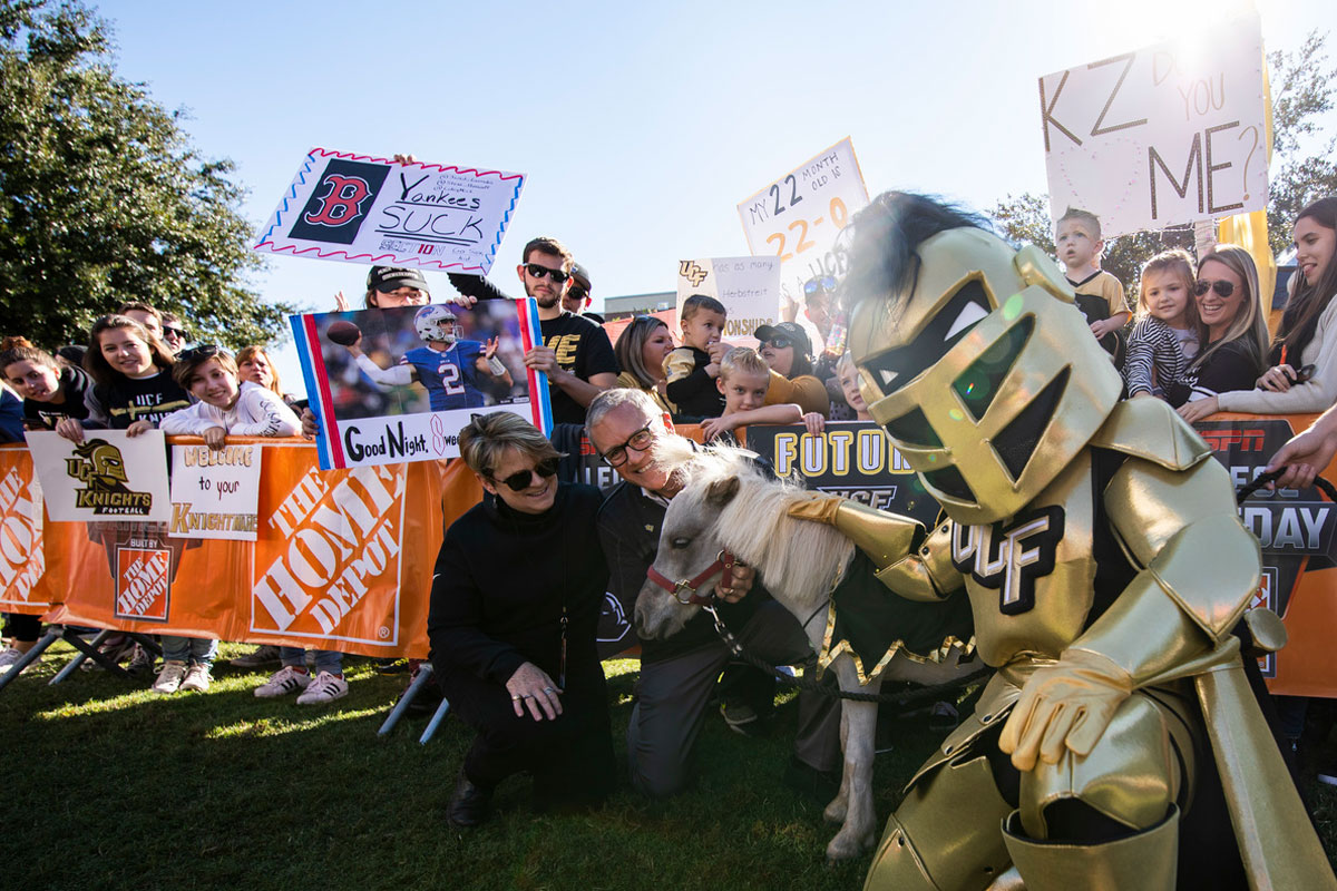 A man and woman kneel next to a mini horse with Knightro