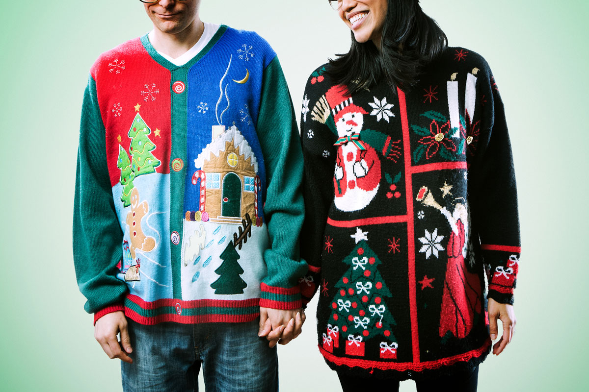 A man and a woman hold hands while wearing ugly holiday sweaters