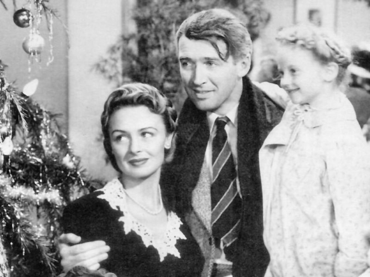 black and white photo of cast of It's A Wonderful Life, man wearing a jacket and tie hugs woman wearing a black and white top and a young girl wearing a white dress
