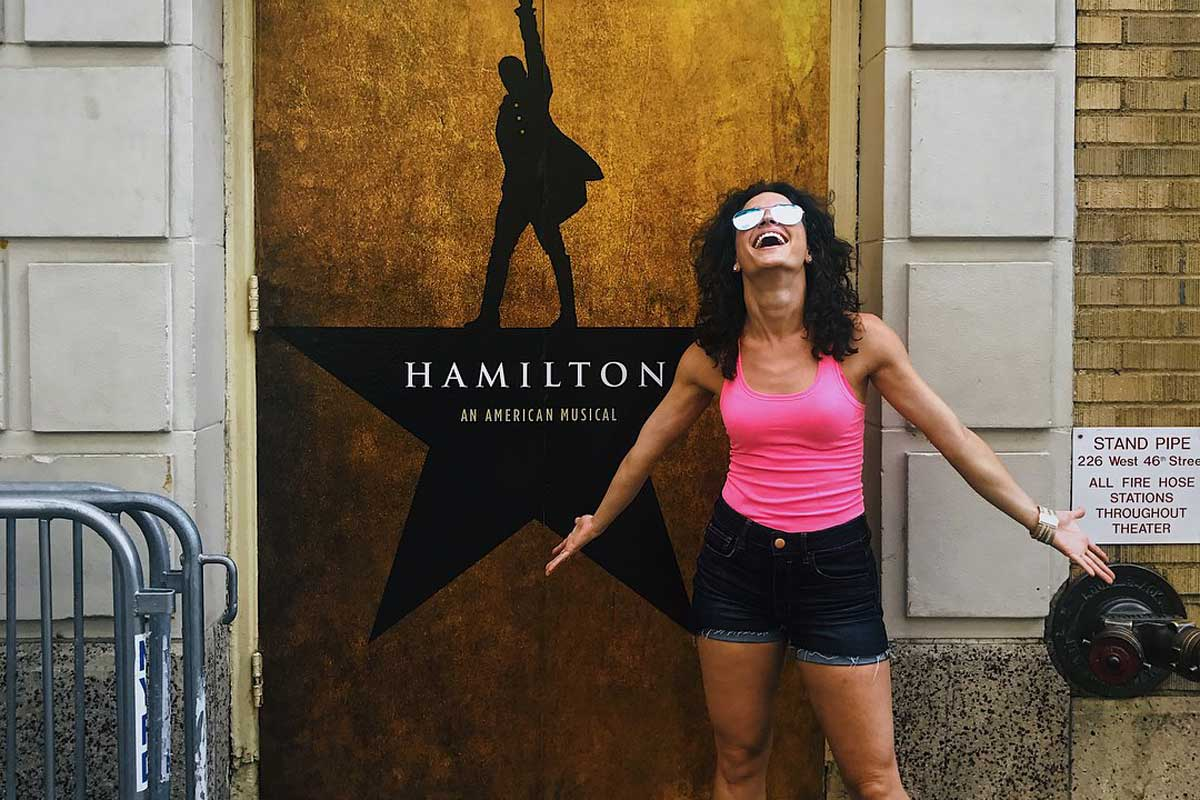 Brunette woman wearing pink tank top stands in front of Hamilton poster