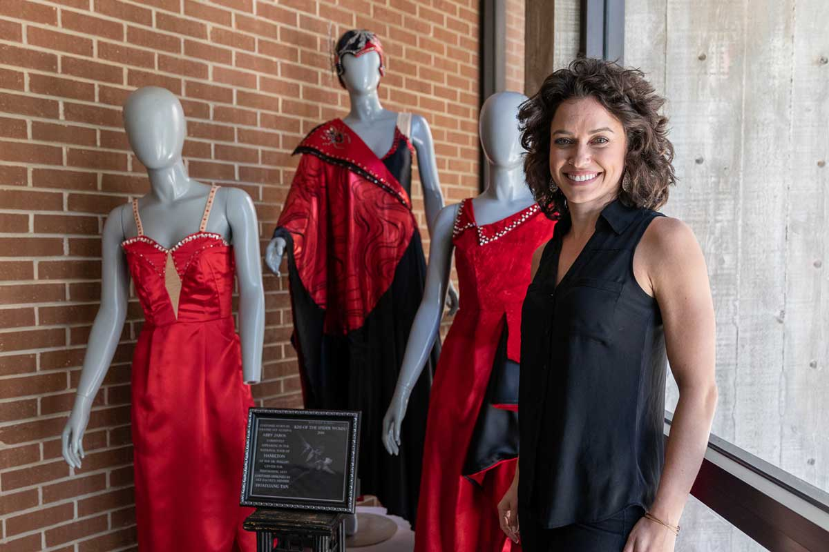 Brunette woman stands in front of three mannequins wearing red dresses