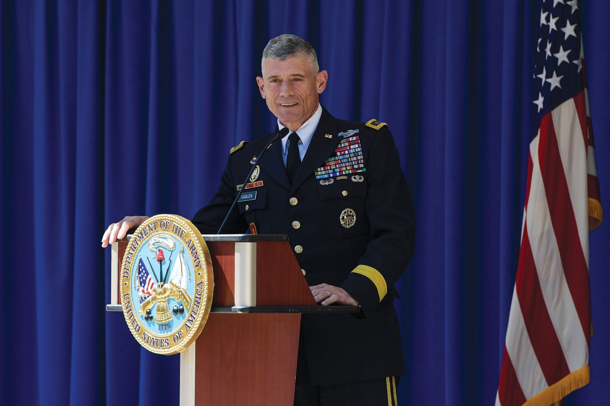 A man in a decorated Army uniform stands at a podium in front of a blue curtain