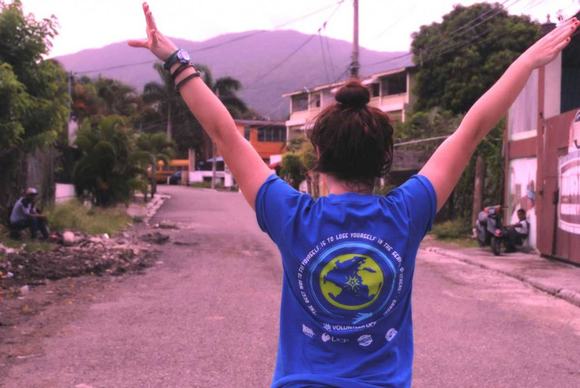 A girl with brown hair wearing a blue T shirt holds her arms up in a V shape on a gravel road with mountains in the background