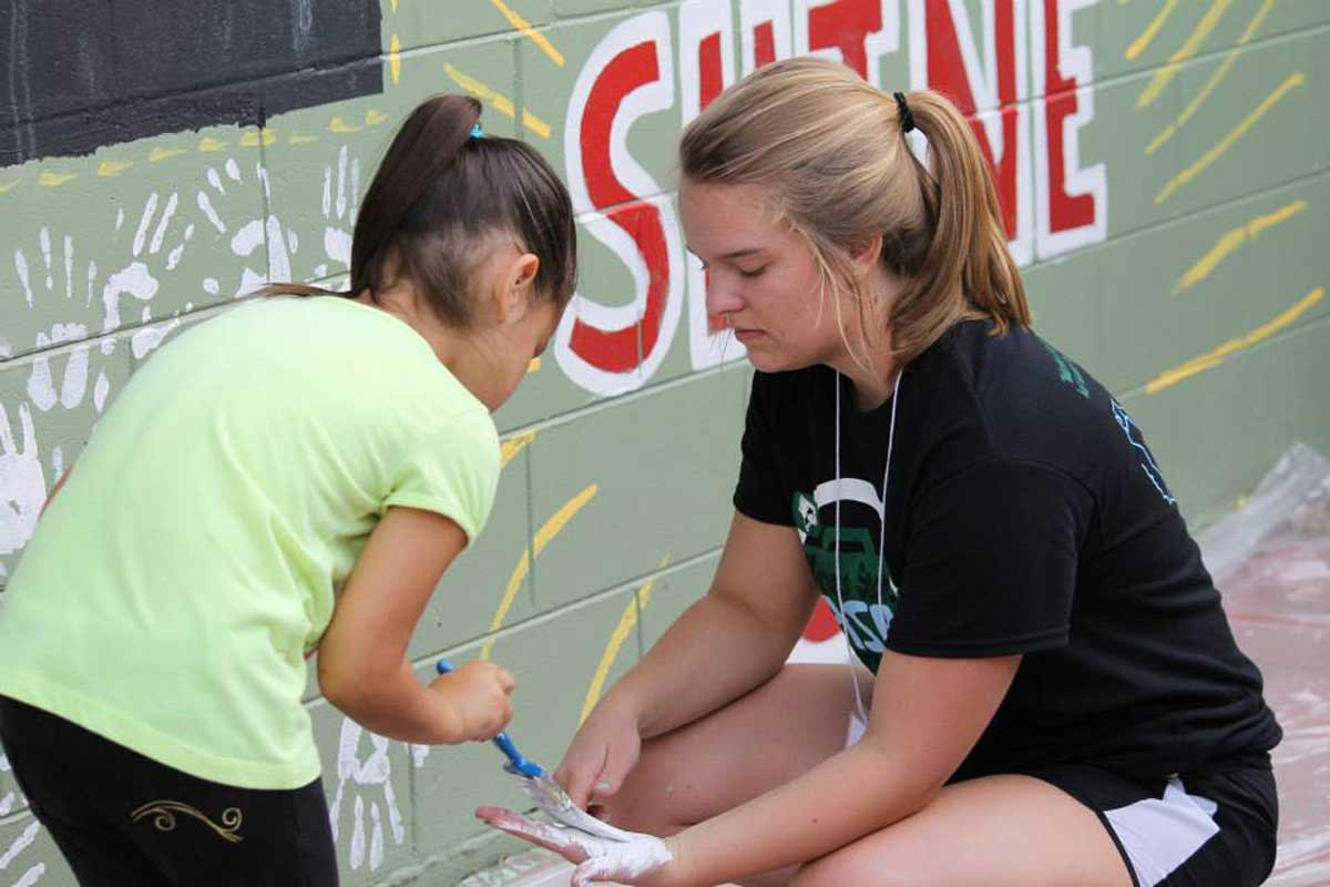 "A young girl wearing a green shirt paints white paint with a blue brush onto the hand of a college-aged girl in front of a green wall with the word ""shine"" painted in red letters."