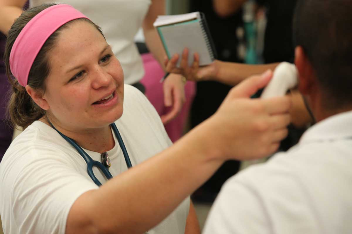 A woman with a pink head band and white t shirt checks someone's temperature with an ear thermometer