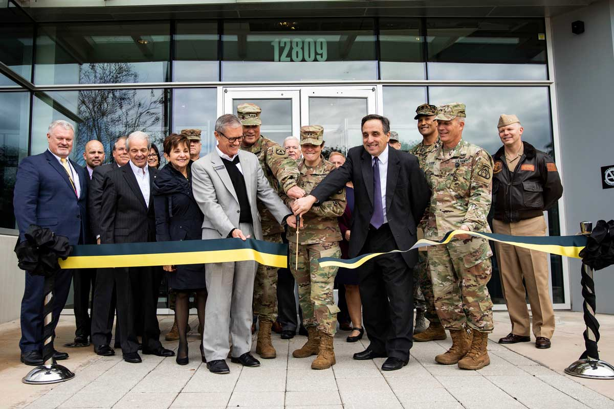 Ribbon cutting ceremony in front of glass building