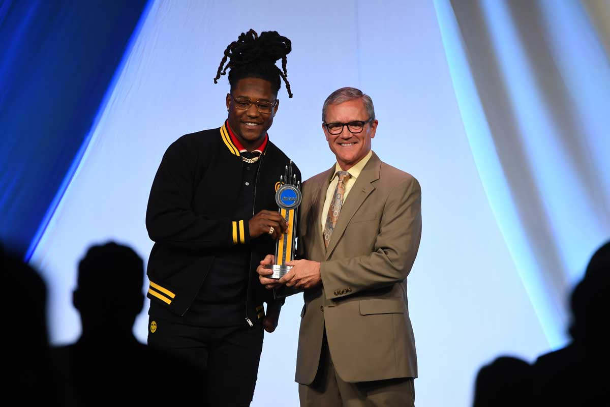 UCF President Dale Whittaker, wearing tan suit, presents gold trophy to Shaquem Griffin, wearing a black jacket with yellow cuffs