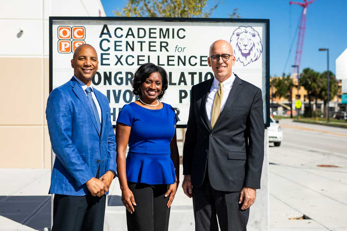 Two men and a woman stand in front of an Academic Center for Excellence sign outside on a sunny day