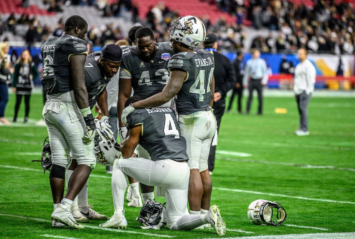 UCF football team huddles on the field