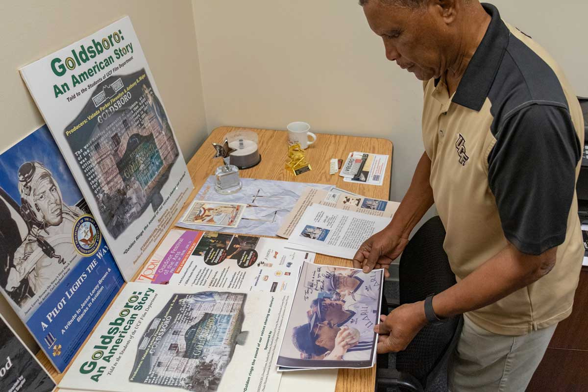 Man looks down at wood table that features various news publications on display