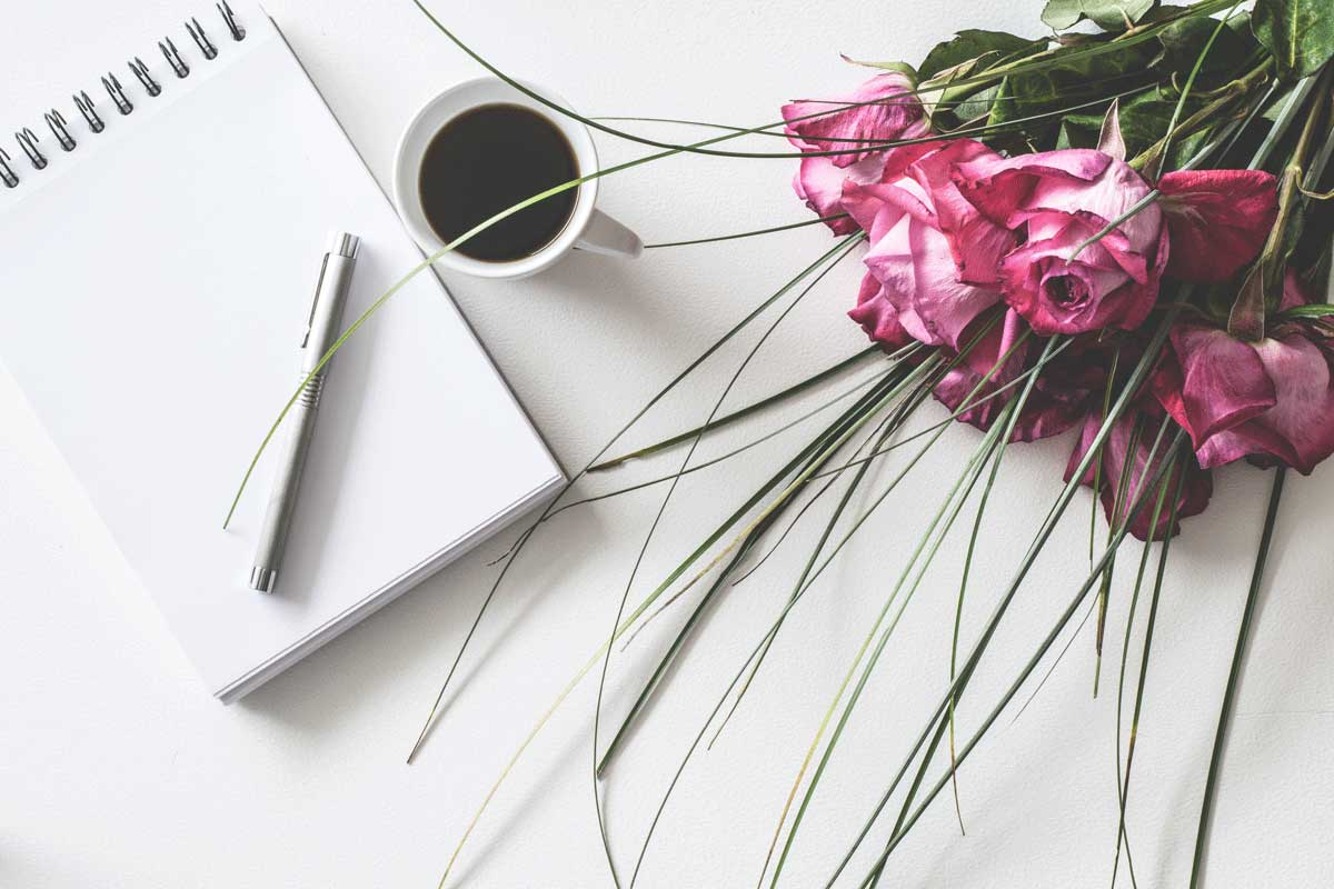 note pad, coffee and bouquet of pink roses on a table