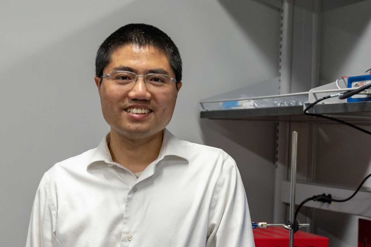 Asian man wearing glasses and white collared shirt stands next to a metal shelf