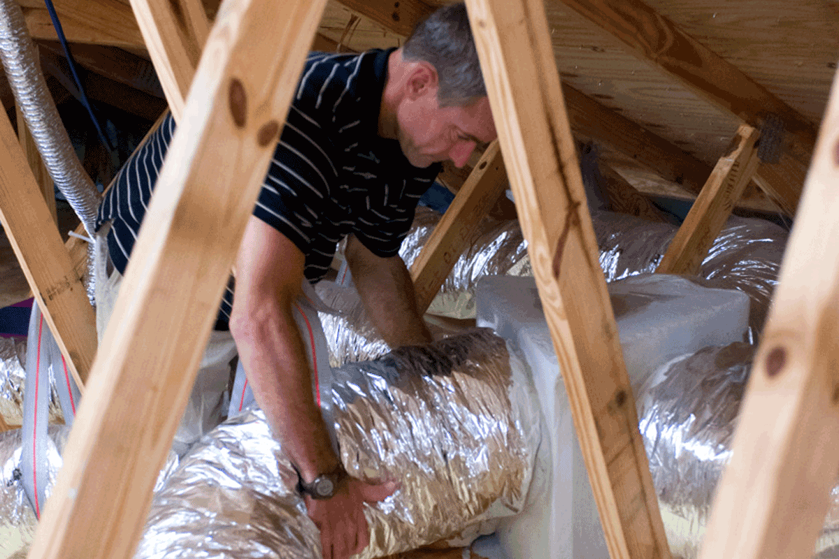 Man connects HVAC system in attic