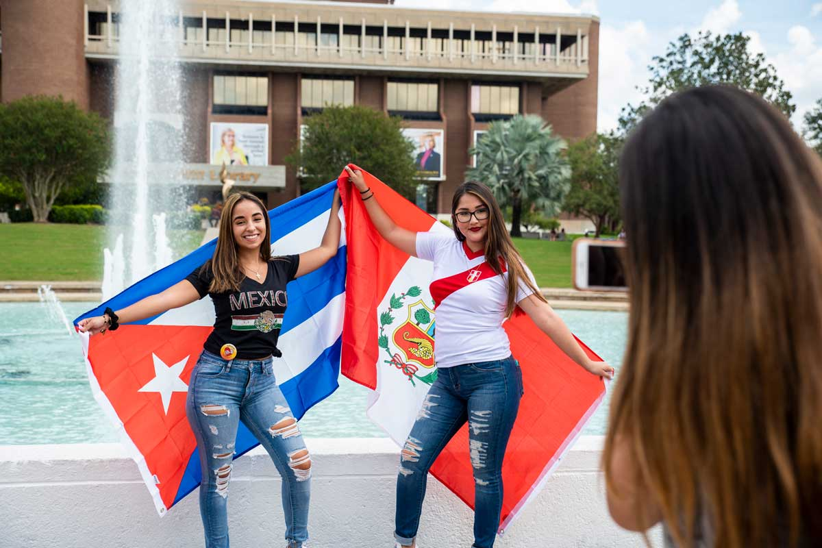 Two women pose with flags in front of fountain