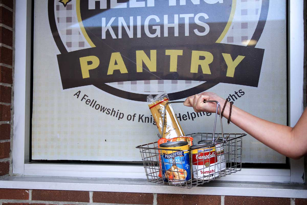 hand holding a basket of non-perishable food in front of Knights Pantry window
