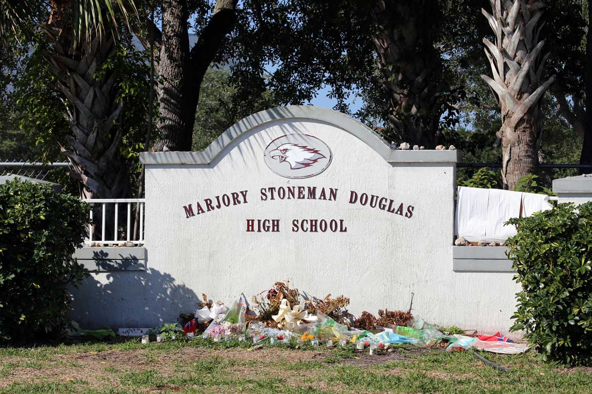 Concrete Marjory Stoneman Douglas High School sign with flowers piled in front of it