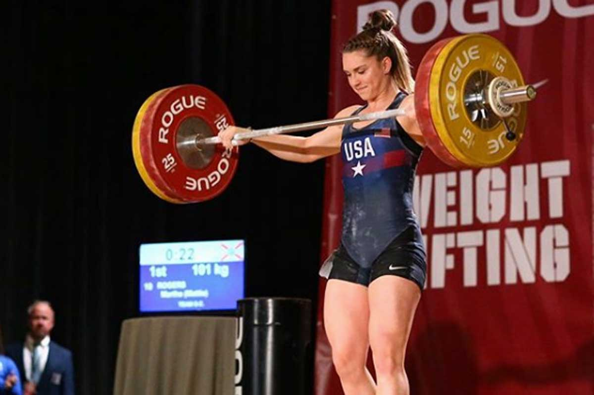 Female in USA singlet holds weight bar at competition