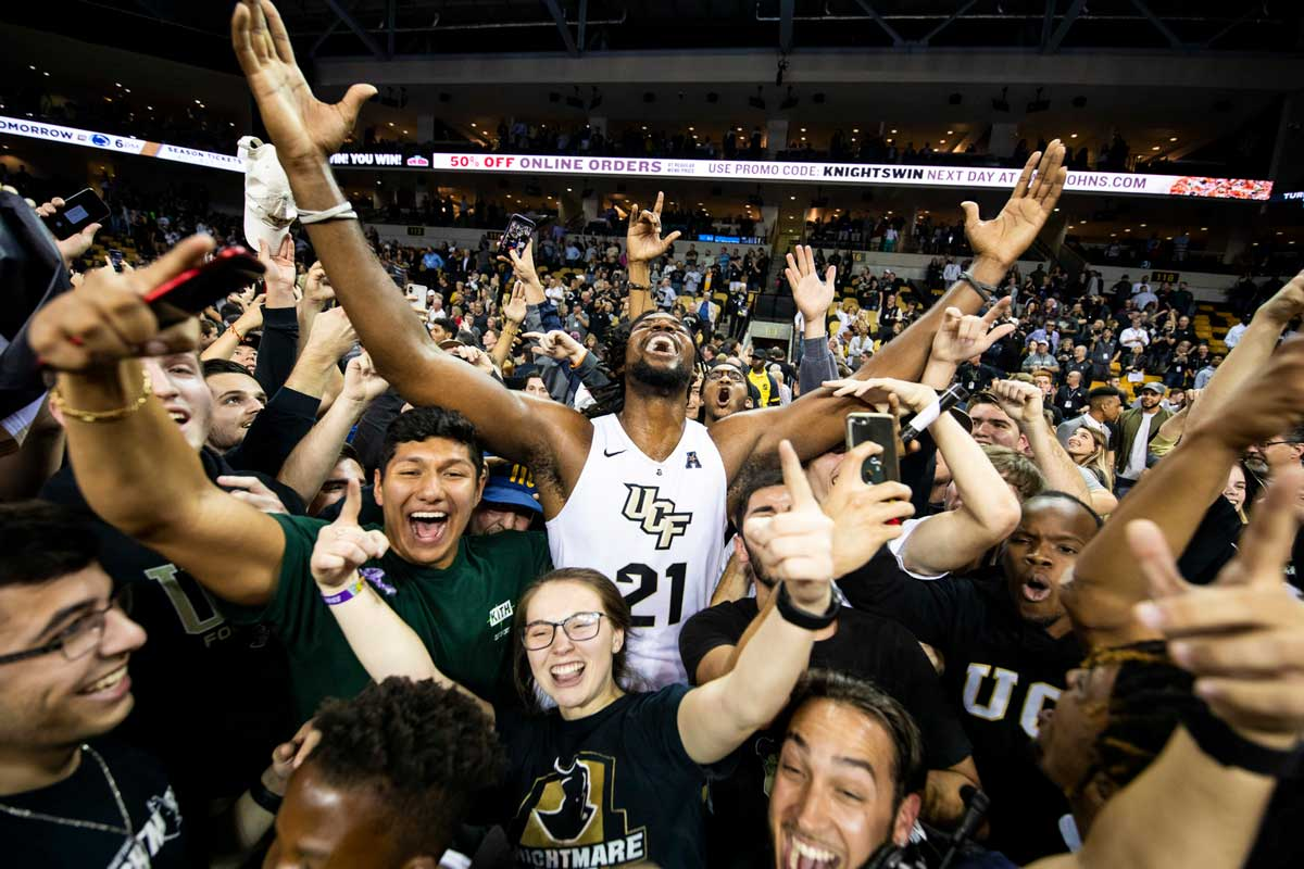 men's basketball player Chad Brown lifts arms in the air to celebrate with fans surrounding him