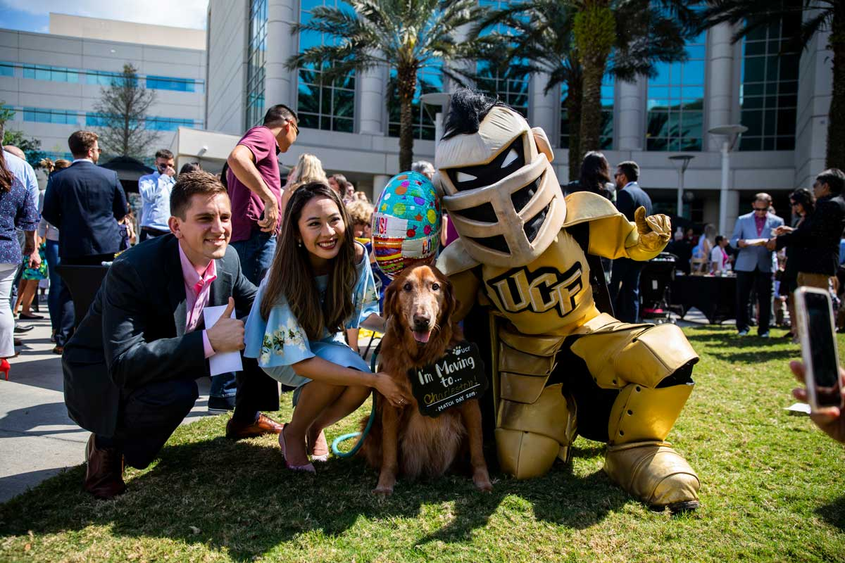 UCF mascot Knightro knees next to a man and woman and golden retriever